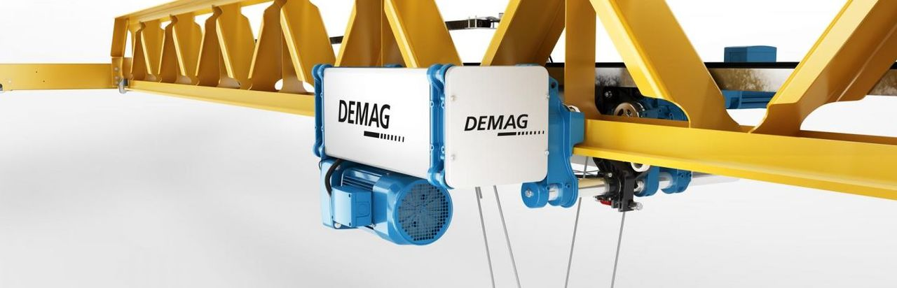 Demag hoist in blue and grey suspended from a yellow metal girder