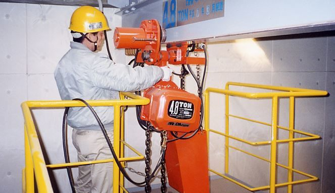 A orange hoist being worked on a girder