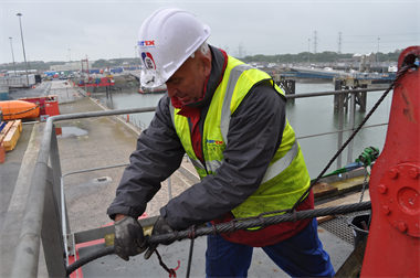 A Steel wire rope labourer preparing a steel wire rope for changing on a crane