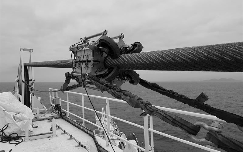 a steel wire rope on a taught line on an offshore vessel with a oil lubricating machine attached to it in black and white