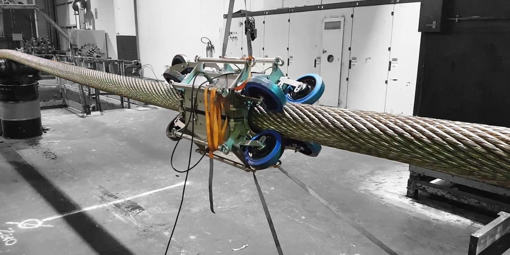 An Image of a steel wire rope inspection device fitted on to a steel wire rope