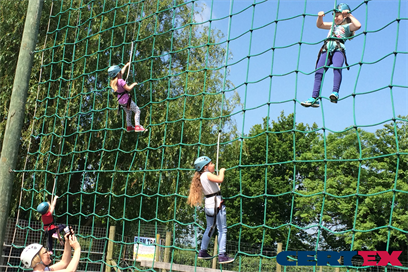 A rope net climbing wall made with steel wire rope and textile to be a combination rope, showing some people climbing up with height safety harnesses and laynards