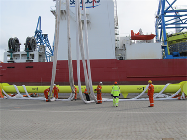 Some engineers managing a large lifting spreader beam and lifting slings next to an offshore vessel