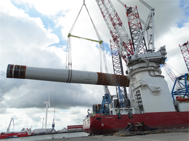 A Wind Turbine Tower being lifting to a vessel