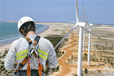 A wind turbine engineer in height safety equipment on a wind turbine with more in the distance