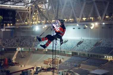 A rigger suspended from a stadium