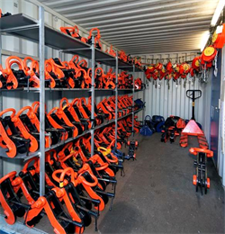 a Metal Storage Container with multiple lifting camps and other lifting apparatus stored inside in vibrant orange