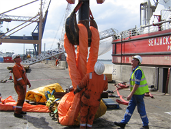 Some riggers placing a large orange textile sling onto a steel hook for use offshore
