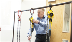 A tutor examining some lifting products such as lever hoists